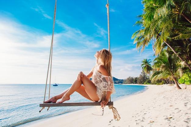 Dziewczyna cieszy się słońcem siedzi na huśtawce