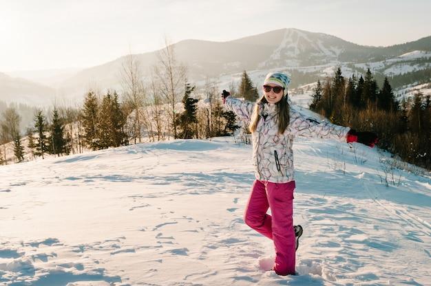 Dziewczyna cieszy się śnieżną zimą góry. spaceruj na łonie natury. sezon mrozu. koncepcja wakacji. trekking w górach. zimno, śnieg na wzgórzach. wędrówki. góral na szczycie w słoneczny zimowy dzień.