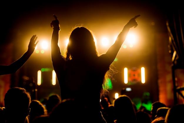 Dziewczyna cieszy się w jej ulubionym festiwalu muzycznym tłum ludzi zespołu.