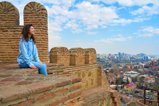 Dziewczyna cieszy się widokiem i ciszą siedząc na murze starożytnej fortecy z widokiem na miasto.