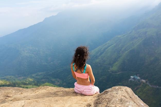 Dziewczyna cieszy się widokiem na góry, stojąc na klifie