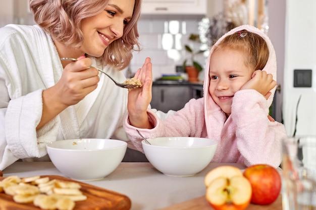 Dziewczyna cieszyć się posiłkiem na śniadanie z mamą
