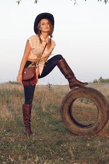 Dziewczyna cowgirl w koszuli dżinsy buty i torbę w pudełku z kołem przy drzewie