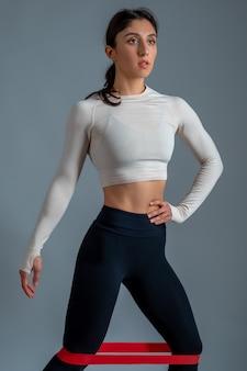 Dziewczyna ćwicząca dolną część ciała z opaską na szarej ścianie
