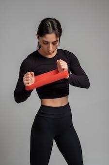 Dziewczyna ćwicząca ramiona z opaską na szarej powierzchni
