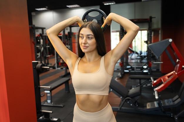 Dziewczyna ćwicząca z dyskiem ze sztangą