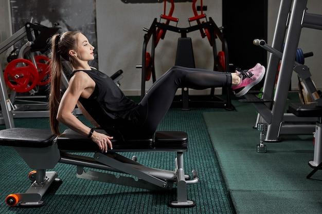 Dziewczyna, ćwiczenia na ławce w siłowni. koncepcja nowoczesnej siłowni z fitness fit zdrowych ludzi.