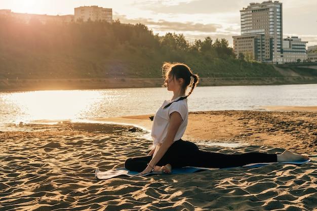 Dziewczyna ćwiczy jogę na brzegu rzeki w promieniach zachodzącego słońca. gołąb stanowią. pojęcie zdrowego stylu życia.