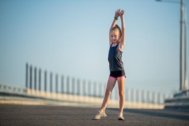 Dziewczyna ćwiczy latem na ulicy, przygotuj się na sztuczkę.