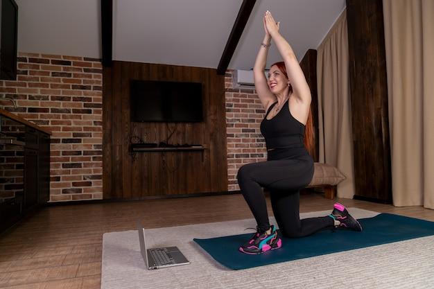 Dziewczyna ćwiczy w domu online i rozciąga mięśnie, przyjmując określoną pozycję