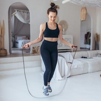 Dziewczyna ćwiczy z skakanka w domu. dopasowana kobieta skakanka.