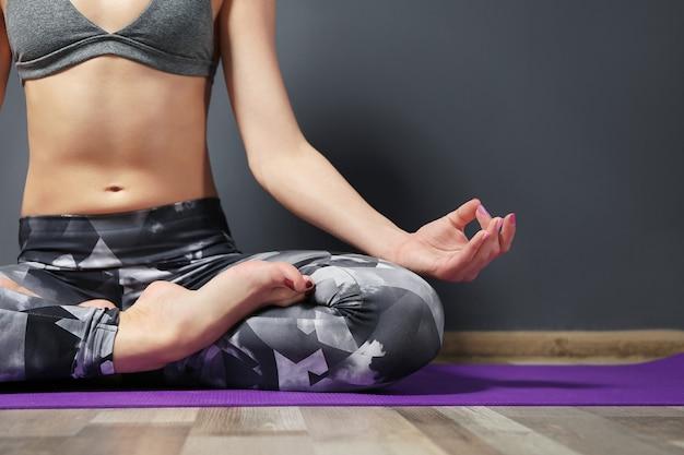 Dziewczyna ćwiczy zaawansowaną jogę na szarej ścianie