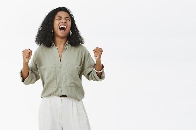 Dziewczyna czująca się szczęśliwa i zdumiona świętująca zwycięstwo, krzycząca głośno z radości i szczęścia, unosząca zaciśnięte pięści
