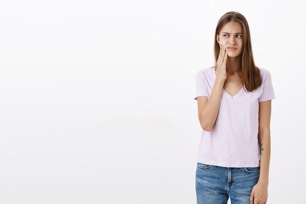 Dziewczyna czuje dyskomfort w ustach z próchnicą stoi zaniepokojona i niezadowolona po wypiciu zimnego napoju patrząc w lewo dotykając policzka i marszczy brwi z powodu bólu zęba pozuje