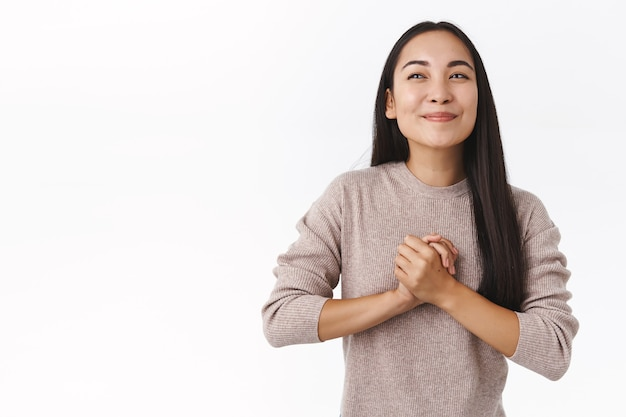 Dziewczyna czuje oczekiwanie i radość, składa dłonie, pociera dłoń i uśmiecha się zachwycona, odwraca wzrok zadowolona, ma coś dobrego na myśli, planuje wielkie wydarzenie, podekscytowana stojąca biała ściana