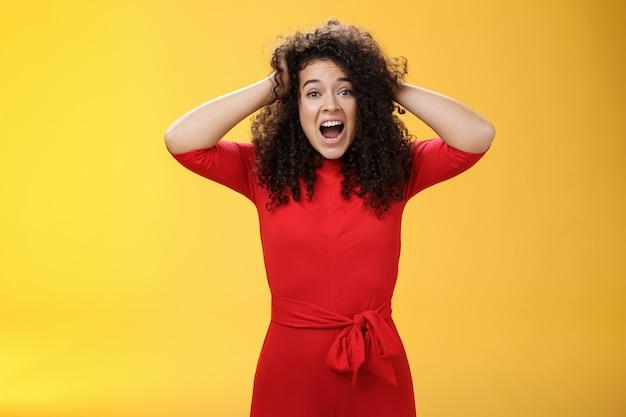 Dziewczyna czuje presję, stojąc niespokojnie w panice, trzymając się za ręce na kręconych włosach, krzycząc na zakłóconą kamerę...