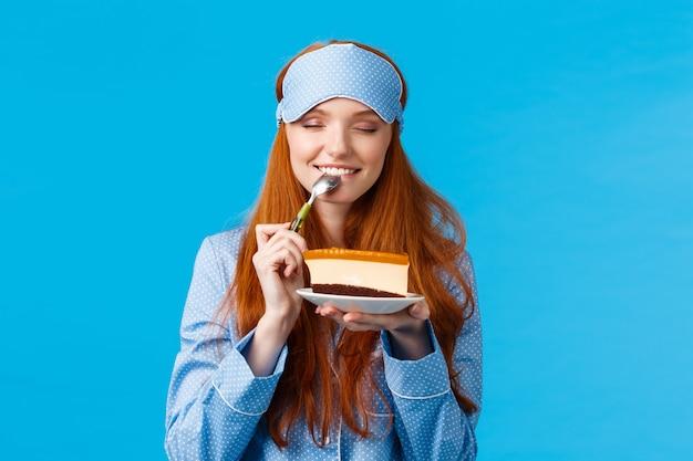 Dziewczyna czuje satysfakcję je słodkiego wyśmienicie deser w ranku. atrakcyjna śliczna kobieta z czerwonymi włosami w bieliźnie nocnej i masce snu, zamknij oczy gryząc smaczne ciasto, trzymając łyżkę blisko oczu