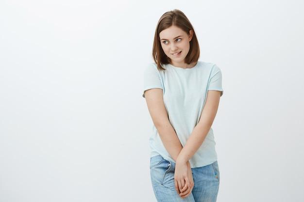 Dziewczyna czuje się nieśmiała stojąc w pobliżu zainteresowania miłością. niezręcznie nieśmiała i niepewna słodka młoda dziewczyna przygryzająca dolną wargę odwracająca wzrok, dotykająca rąk i pochylona, rozmawiając z popularnym atrakcyjnym facetem, którego lubi