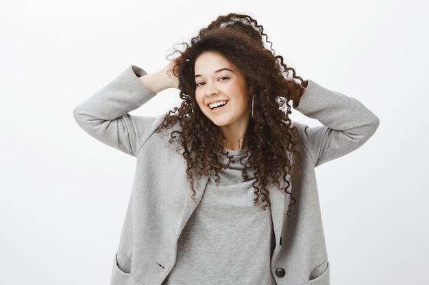 Dziewczyna czuje się odprężona i beztroska po wizycie w spa. radosna jasna europejska suczka o kręconych włosach w szarym płaszczu, dotykająca loków i szeroko uśmiechnięta