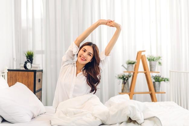Dziewczyna czuje się relaksując i cieszyć się czasem na łóżku w domu
