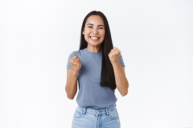 """Dziewczyna czuje się szczęśliwa, odczuwa ulgę, gdy pokazuje się okazja. atrakcyjna uśmiechnięta azjatycka kobieta z pięścią, triumfująca, mówiąca """"tak"""", stojąca biała ściana zadowolona ze wspaniałego wyniku"""
