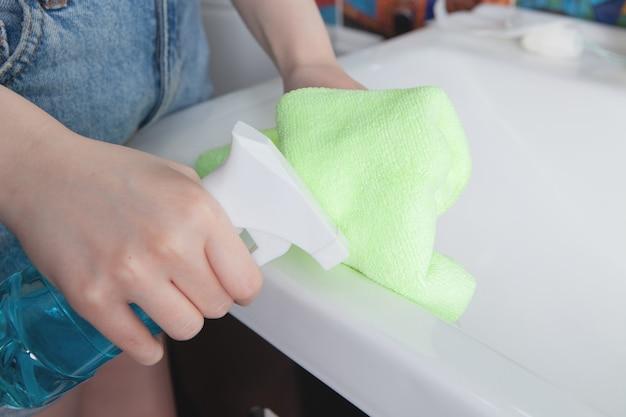 Dziewczyna czyści zlew szmatką
