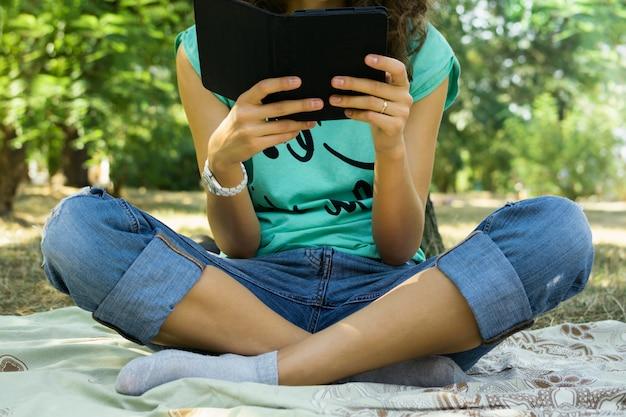 Dziewczyna czyta e-book na łące