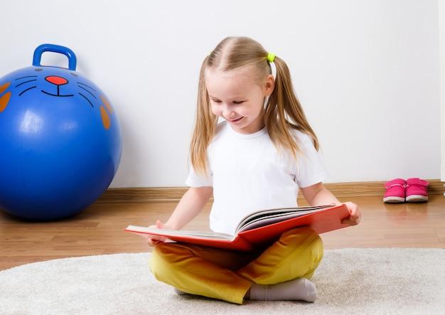 Dziewczyna czyta książkę. dziecko czyta książkę na podłodze.
