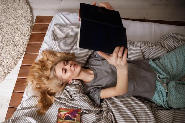 Dziewczyna czyta książkę w łóżku. widok z góry