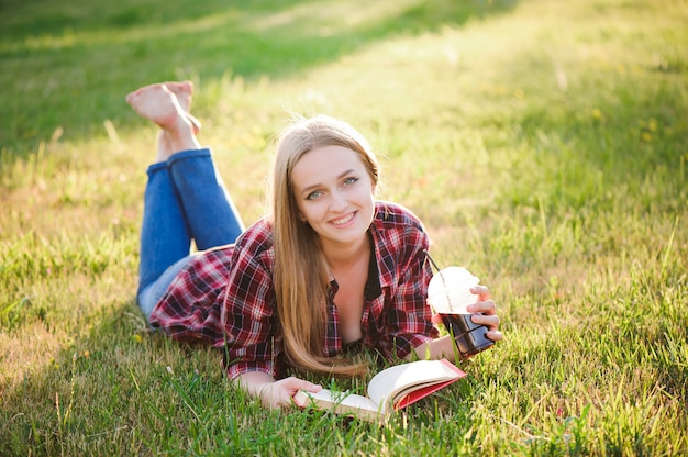 Dziewczyna czyta książkę w parku, kobieta, zieleń.