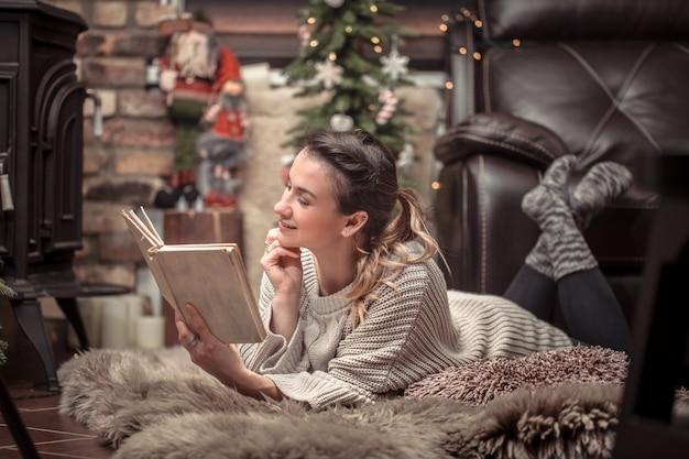 Dziewczyna czyta książkę w przytulnej domowej atmosferze przy kominku