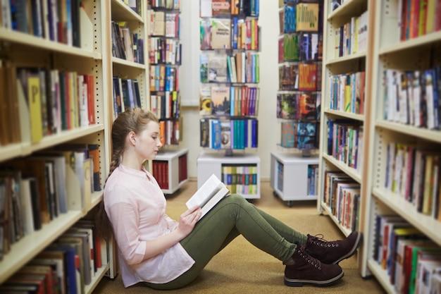 Dziewczyna czyta w bibliotece