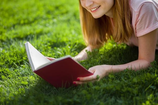 Dziewczyna czytająca książkę w parku. ścieśniać