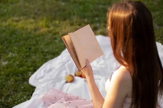 Dziewczyna czytająca książkę z pustą stroną siedzącą na trawie w parku