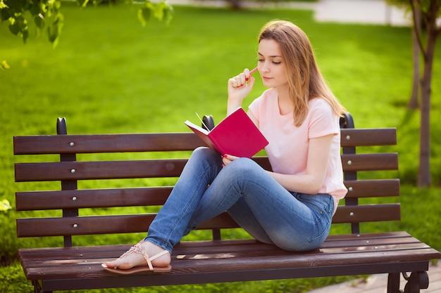 Dziewczyna czytająca notebook na ławce w parku