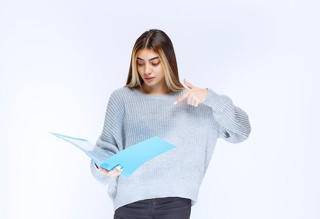 Dziewczyna czytająca raporty w niebieskiej teczce i robiąca uwagi.