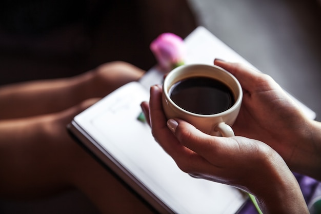 Dziewczyna, czytanie książki i picie kawy, piękna róża. rano, hobby, kwiaty, nauka