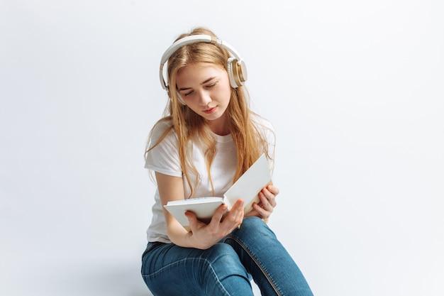 Dziewczyna, czytanie książki i słuchanie muzyki