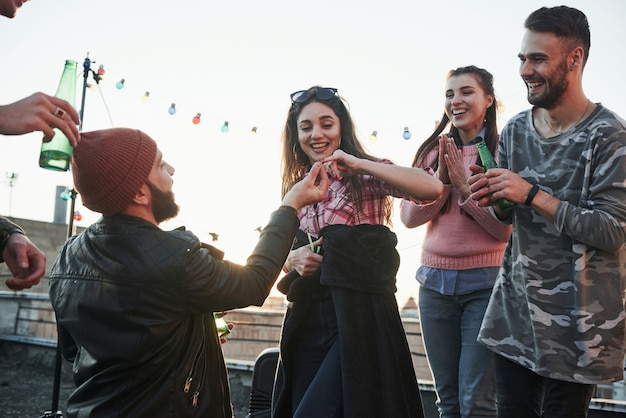 Dziewczyna daje jej palec. deklaracja miłości na dachu w towarzystwie przyjaciół