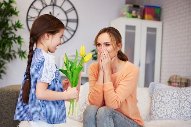 Dziewczyna daje mamie kwiaty i kartkę z życzeniami