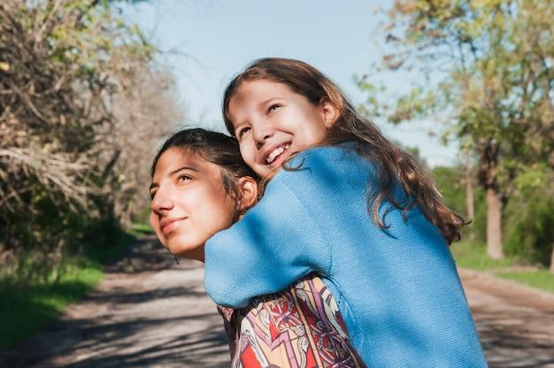 Dziewczyna daje piggyback jedzie jej młodszej siostrze na słonecznym dniu