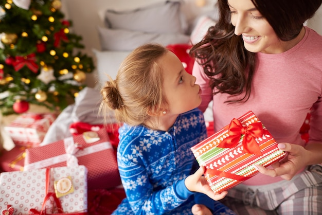 Dziewczyna daje prezent pod choinkę swojej mamie