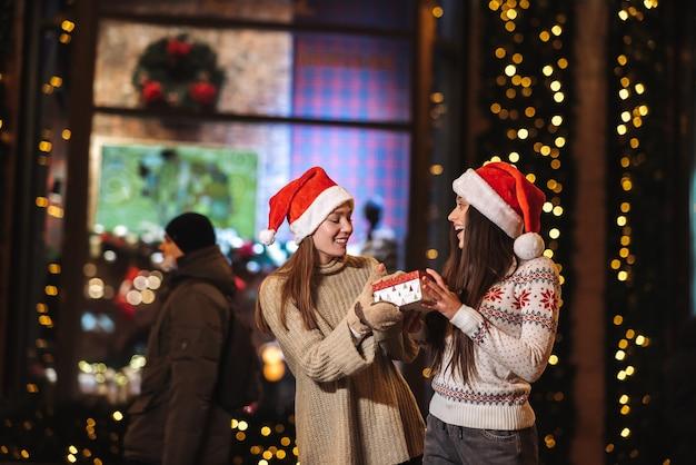 Dziewczyna daje prezent swojej koleżance na ulicy. portret szczęśliwy śliczni młodzi przyjaciele