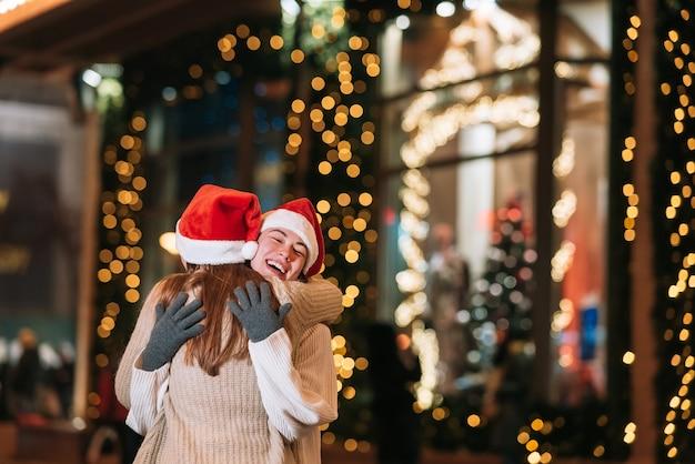 Dziewczyna daje prezent swojej koleżance na ulicy. portret szczęśliwych uroczych młodych przyjaciół