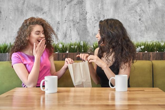 Dziewczyna daje teraźniejszości zdziwiony przyjaciel w kawiarni.