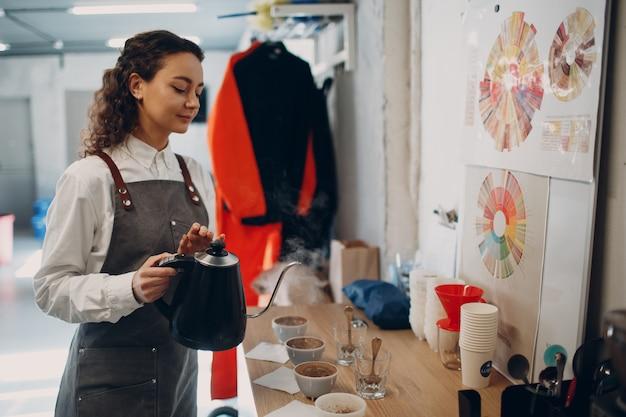 Dziewczyna degustatorka filiżanek z nalewaniem czajnika degustacja degustacja test jakości kawy. bańki do kawy.