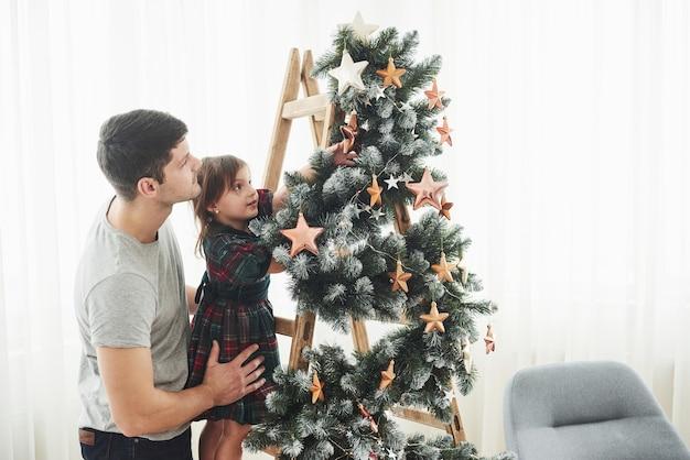 Dziewczyna dekoruje piękną choinkę z gwiazdami, podczas gdy jej ojciec ją trzyma.