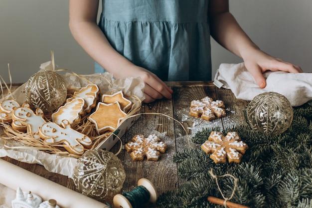 Dziewczyna dekoruje świąteczne ciasteczka