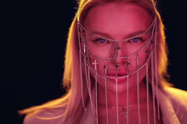 Dziewczyna dj przy pilocie z biżuterią w postaci łańcuchów na twarzy