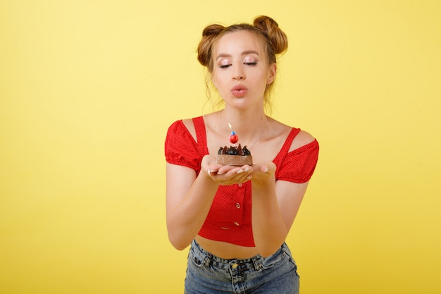 Dziewczyna dmucha świeczkę na torcie na żółtej przestrzeni. święto. wszystkiego najlepszego z okazji urodzin